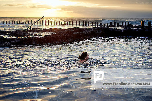 Woman swimming in coastal pool at sunset  Las Palmas  Gran Canaria  Canary Islands  Spain