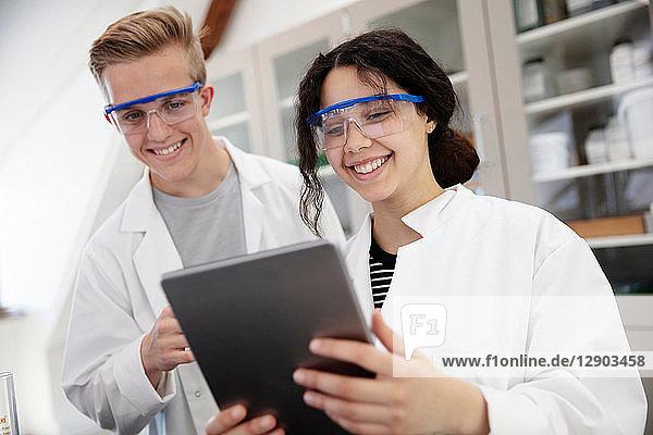 SchülerInnen mit digitalem Tablett im Labor