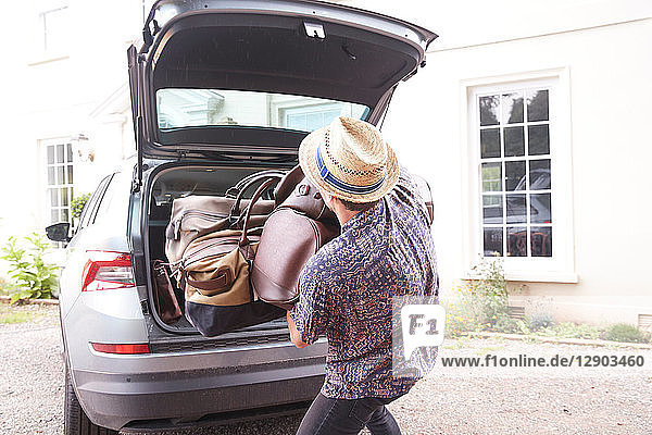 Young man in trilby removing luggage from car boot outside hotel  rear view