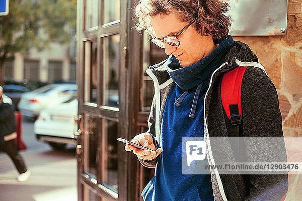 Mann liest Textnachricht vor der Tür