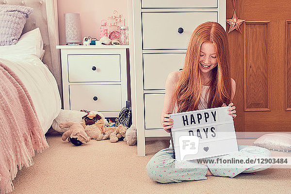 Girl holding up sign on bedroom floor