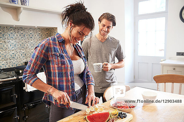 Couple chatting while slicing fresh fruit at kitchen table