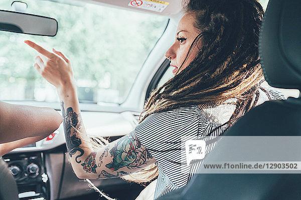 Frau  die dem Fahrer im Fahrzeug den Weg weist