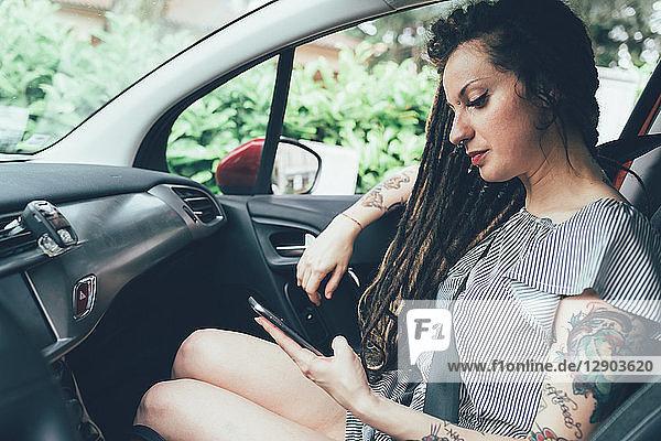 Frau benutzt Mobiltelefon im Auto