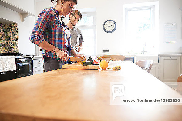 Couple slicing fresh fruit at kitchen table