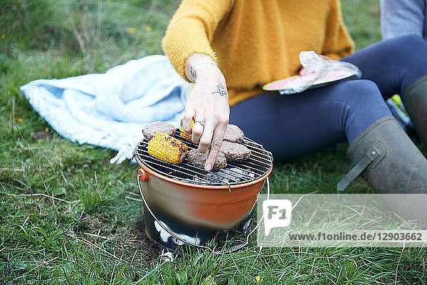 Woman and boyfriend sitting in rural field cooking on barbecue grill  cropped