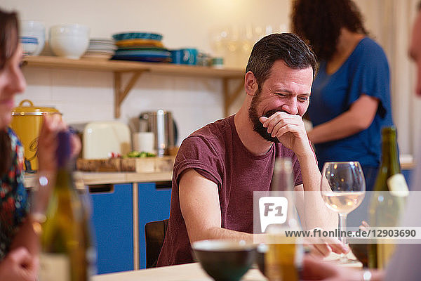 Friends laughing at dinner party