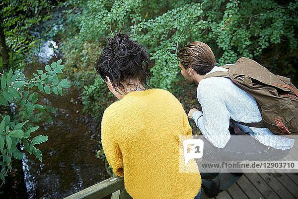 Hiker couple looking over wooden bridge