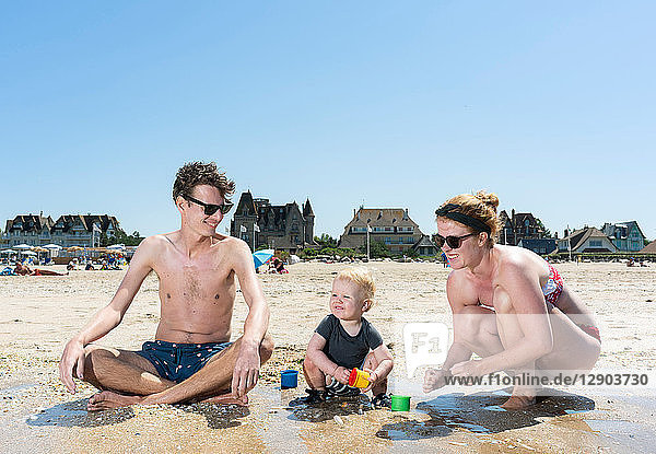 Parents playing with toddler on beach