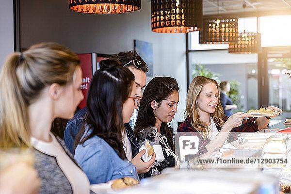 Junge männliche Studenten und Freundinnen an der Café-Theke