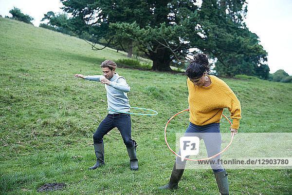 Couple hula hooping in field