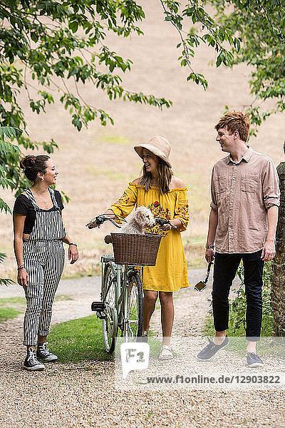 Freunde beim Spaziergang mit Fahrrad und Haushund auf dem Land Freunde beim Spaziergang mit Fahrrad und Haushund auf dem Land