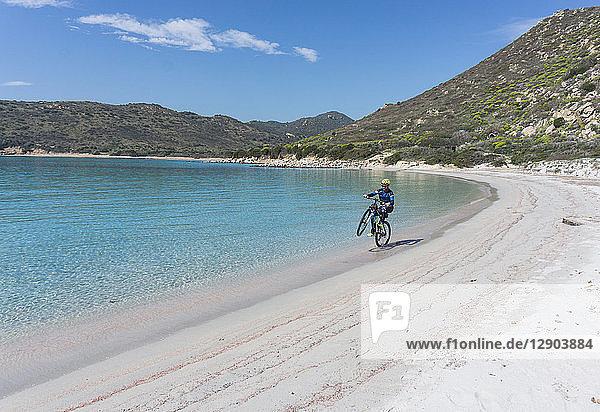 Radfahrer im Wheelie am Strand  Villasimius  Sardinien  Italien