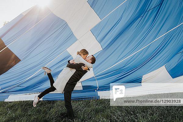Frisch verlobtes Paar küsst sich  im Hintergrund ein Heißluftballon
