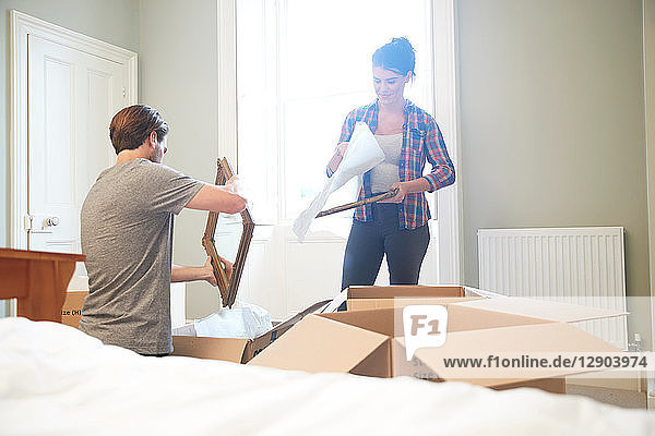 Couple packing mirror into cardboard box