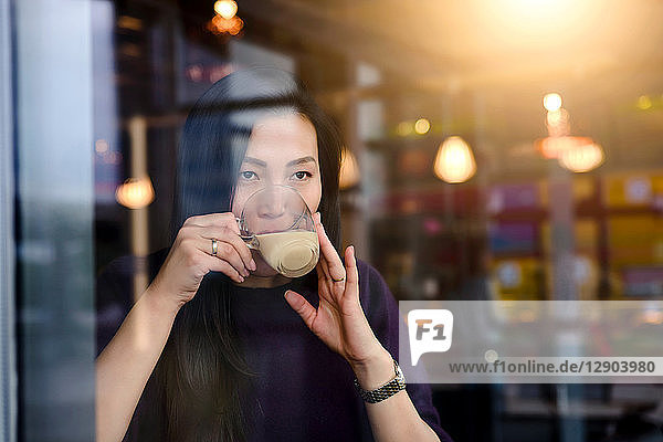 Mid adult woman drinking coffee in cafe window seat