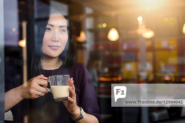 Mid adult woman with coffee looking out from cafe window seat