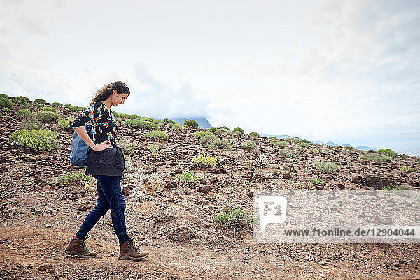Woman hiking on dirt track in arid landscape  Las Palmas  Gran Canaria  Canary Islands  Spain
