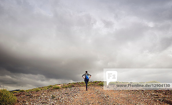 Woman hiking up hill on dirt track  rear view  Las Palmas  Gran Canaria  Canary Islands  Spain