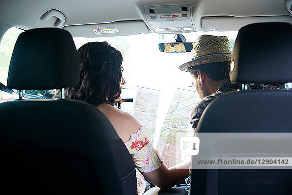 Couple sitting in car looking at folding map  rear view