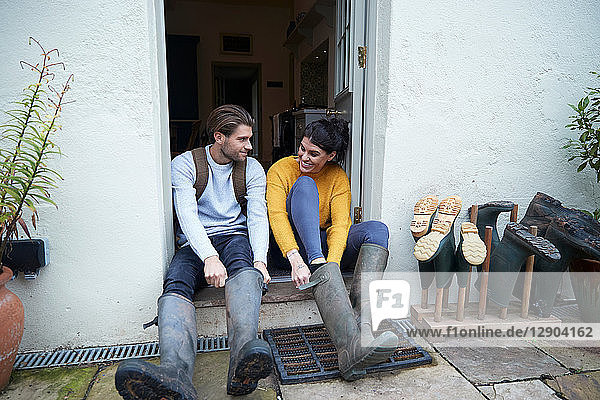 Hiker couple on doorway putting on wellies
