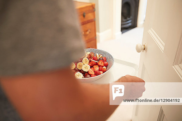 Young man carrying breakfast tray into bedroom  close up