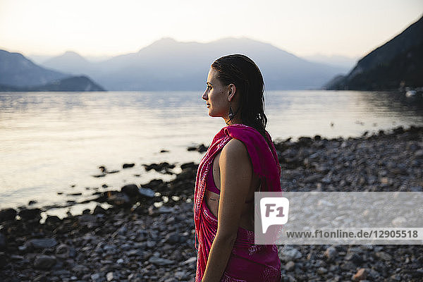 Beautiful young woman at the lakeside looking at distance