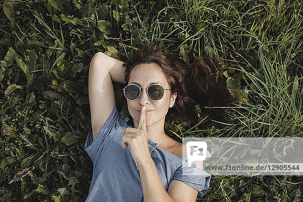 Portrait of smiling woman wearing sunglasses lying in grass