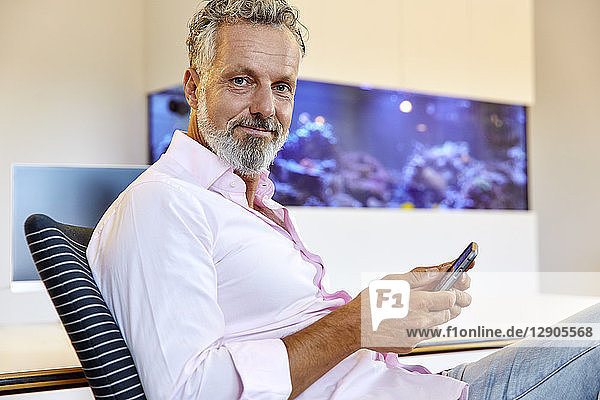 Portrait of confident businessman sitting in office using cell phone