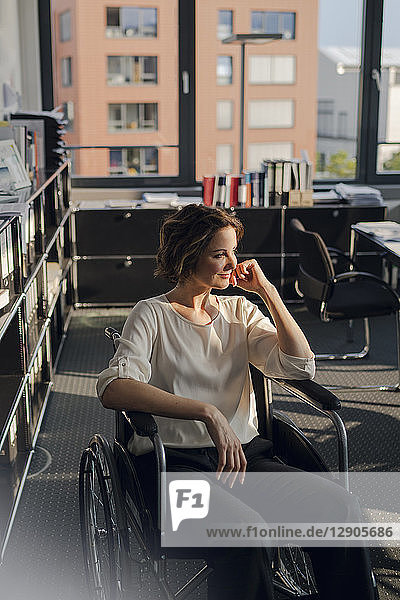 Disabled business woman sitting in wheelchair  smiling