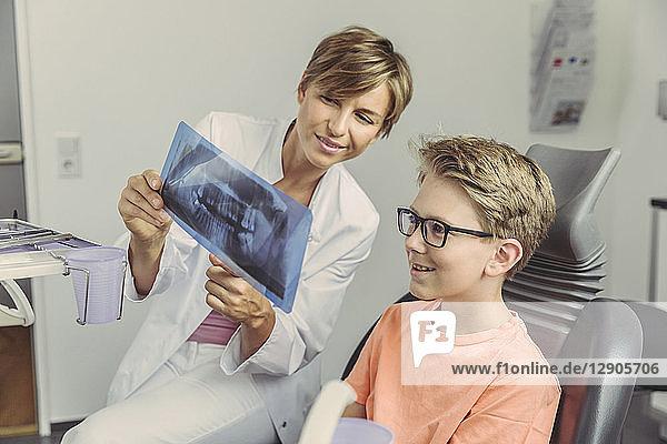 Female dentist explaining boy a x-ray image