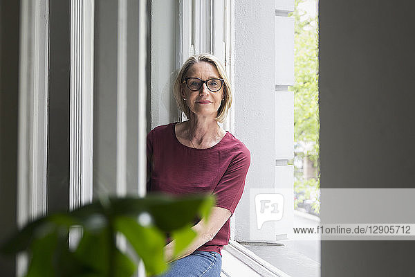 Portait of confident mature woman at the window
