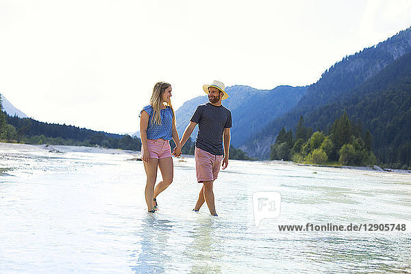 Young couple walking in water