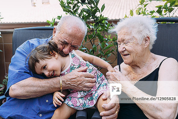 Grandparents and granddaughter having fun together on terrace