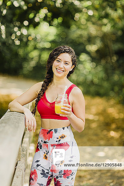Young woman drinking juice after practicing Pilates in an urban park
