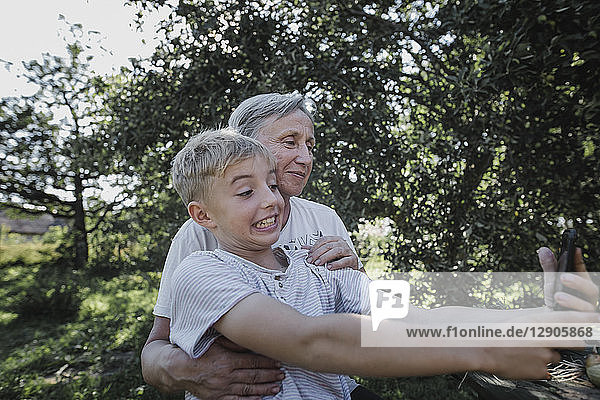 Grandmother and playful grandson taking a selfie in garden