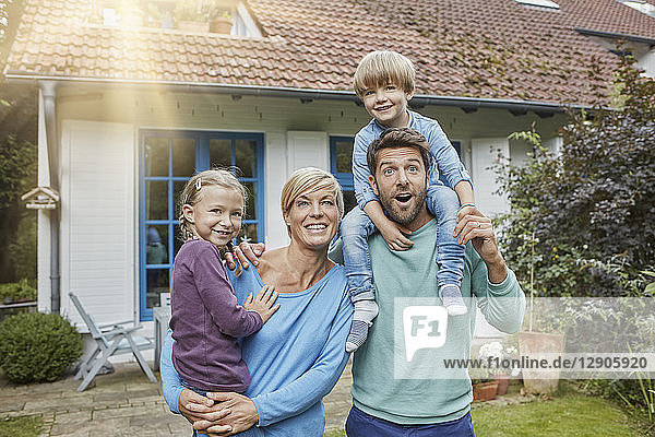 Portrait of happy family with two kids in front of their home