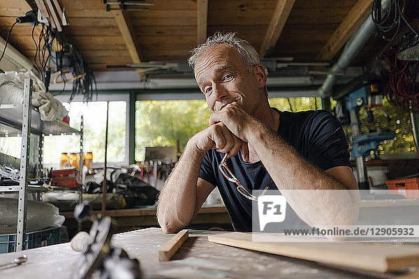 Portrait of confident mature man at workbench in his workshop