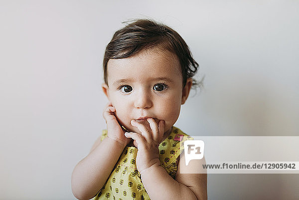 Portrait of baby girl with hand on mouth on white background