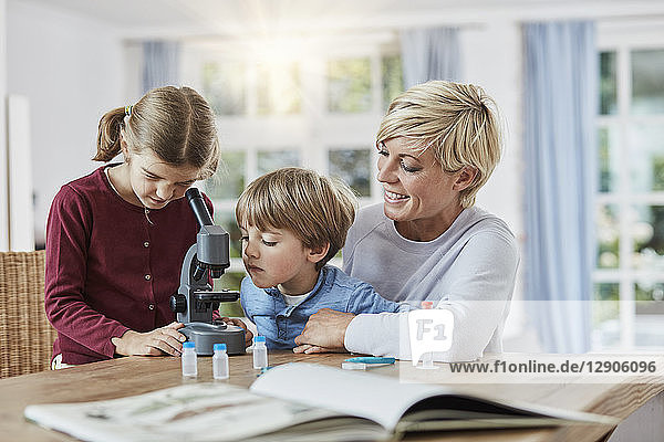 Mother with daughter and son using microscope at home