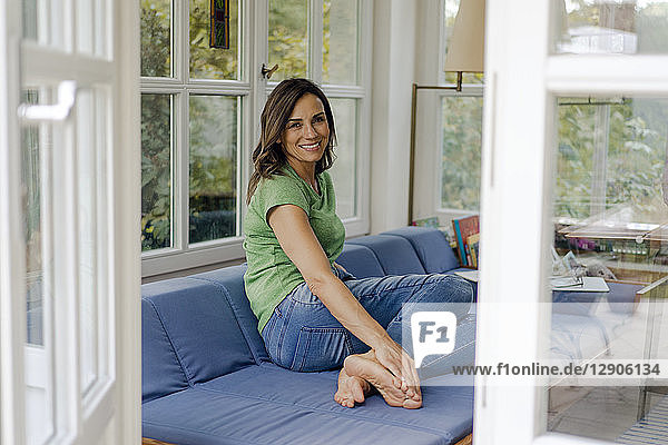 Smiling mature woman sitting on couch at home