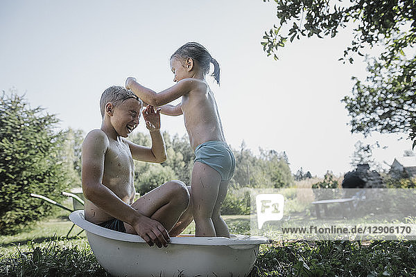 Brother and sister playing with water in little bath tub in garden