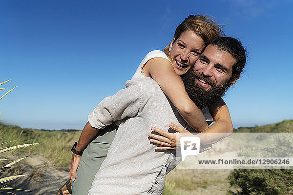 Young man carrying his girlfriend piggyback in the dunes