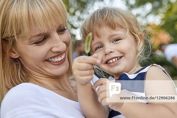 Happy mother with her daughter holding a stalk outdoors