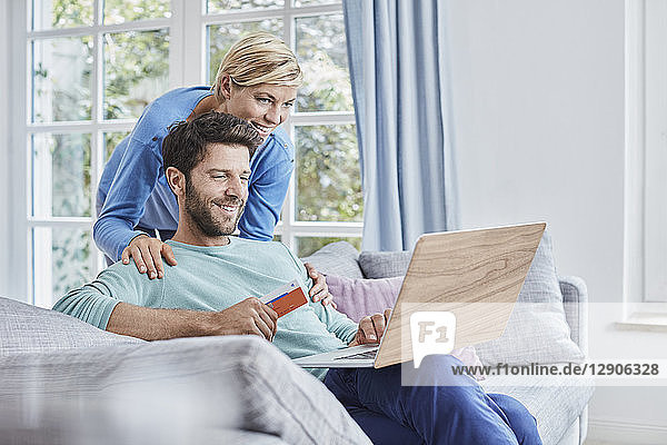 Happy couple at home shopping online