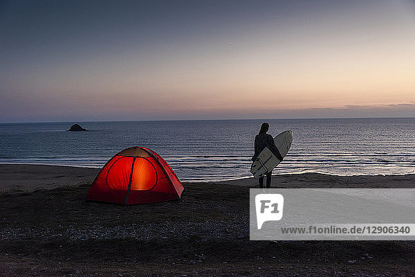 Young woman camping on the beach  carrying surfboard at night