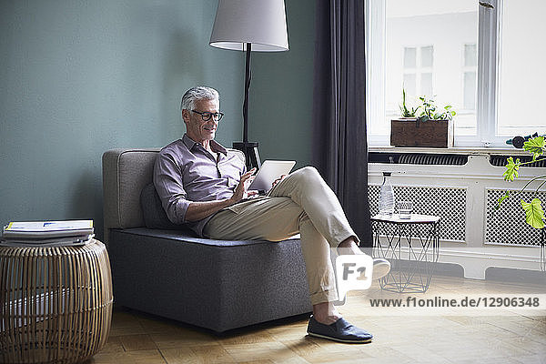 Mature man using tablet at home