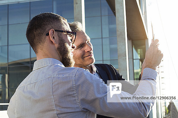 Two businessmen sharing a tablet outdoors