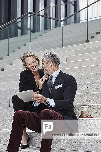 Two smiling business people with tablet sitting together on stairs