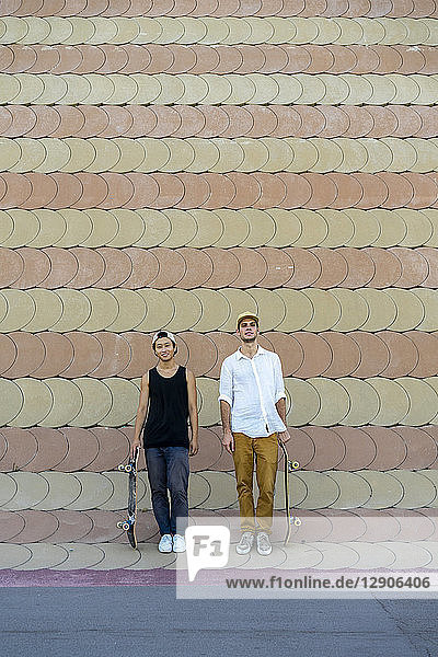 Two smiling young men with skateboards standing at a wall